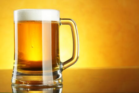 froth: Beer mug with froth over yellow background  Stock Photo