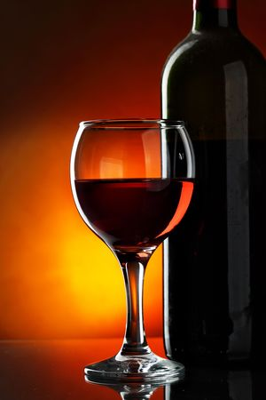 Glass and bottle of red wine over dark red background Stock Photo - 5897008