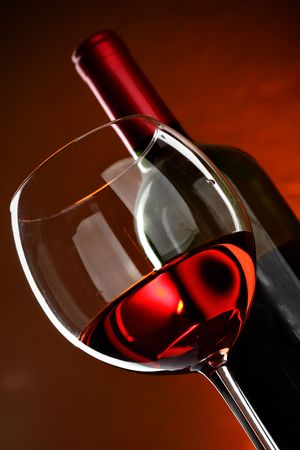 Glass and bottle of wine over red background photo