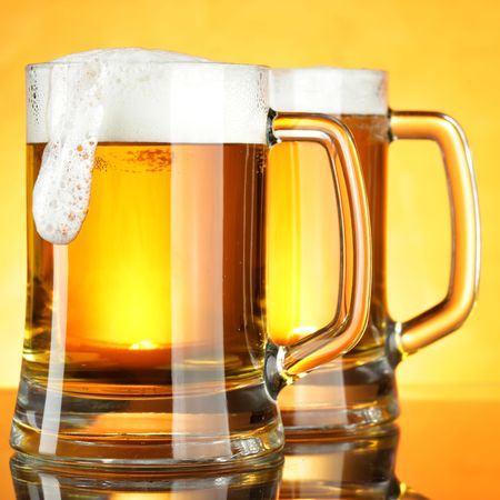 Beer mugs with froth over yellow background photo