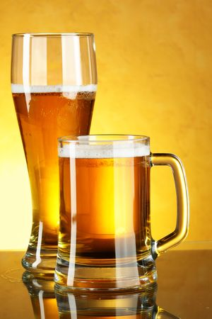 Glass and mug of beer over yellow background photo
