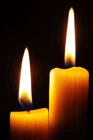 Two burning candles over a black background photo