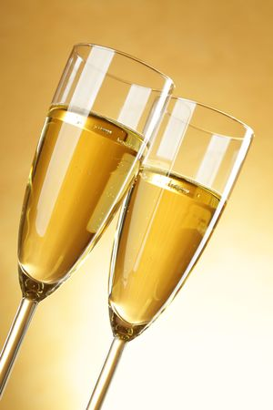 Two glasses of champagne over yellow background photo