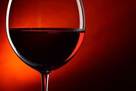 tasting: Glass of red wine close-up over deep red background