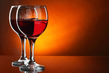 Two glasses of red wine close-up over red background photo