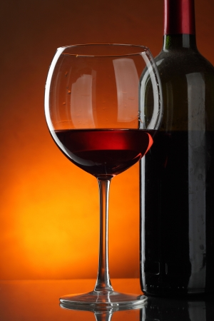 dark glasses: Glass and bottle of red wine over dark red background