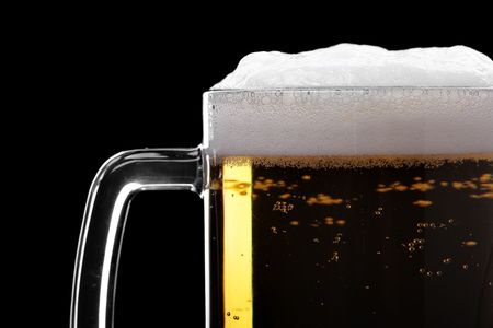 Beer mud with froth close-up isolated over the black background photo