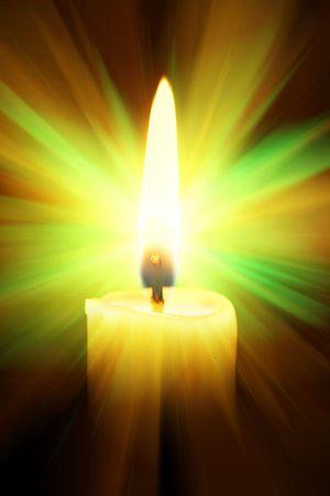 Single burning burning candle over a black background photo