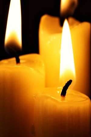 Three burning candles over a black background photo