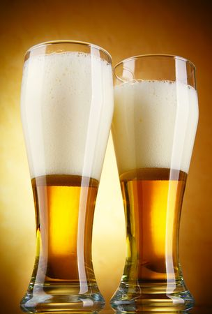 Beer with froth close-up over yellow background  photo