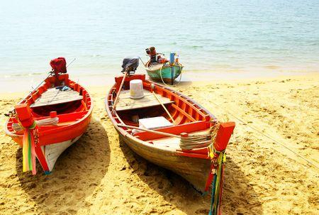 Three fsherman boats close-up at sandy beach photo