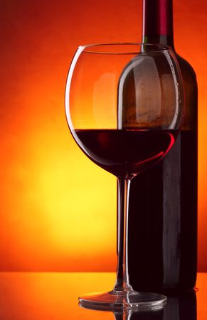 taster: Glass and bottle of red wine over red background