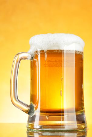 mug of ale:  Beer mug with froth over yellow background Stock Photo