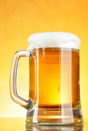 vasos de cerveza:  Jarra de cerveza con espuma sobre fondo amarillo