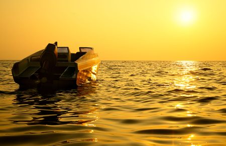 Small motorized boat and sea at sundown photo