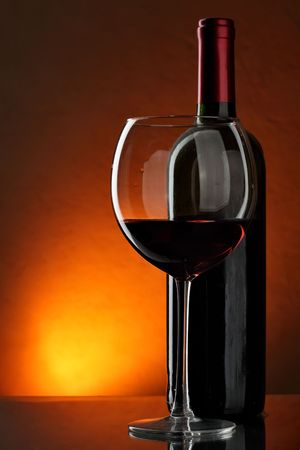 Glass and bottle of red wine over red background