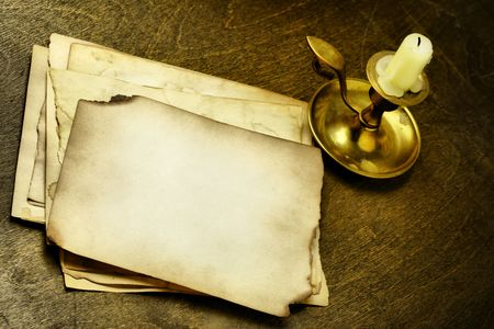 witchery: Old pages and candle on wooden table
