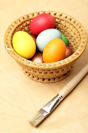 Painted easter eggs in straw bowl and beush photo