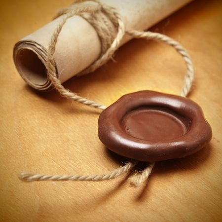 credence: Scroll with wax seal on a wooden table