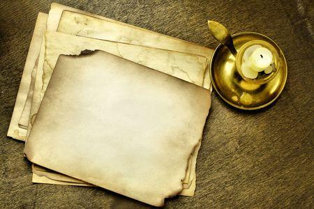 Las páginas antiguas y vela en la mesa de madera Foto de archivo