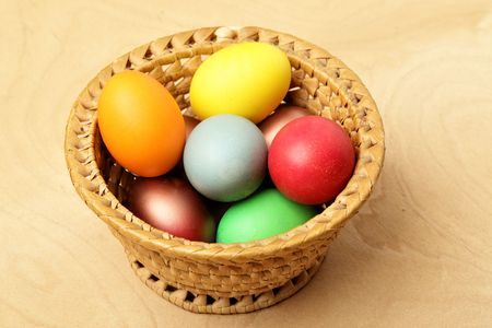 Painted easter eggs in straw bowl on wooden table photo