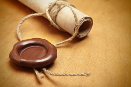 Scroll with wax seal on a wooden table photo