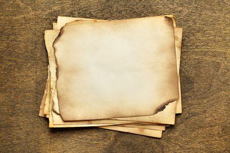 papel quemado: Pila de papeles viejos en una tabla de madera Foto de archivo