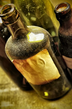 Old tagged bottles with transparent liquid close-up photo