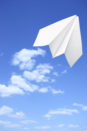 Paper plane taking off. Sky and clouds in the background photo