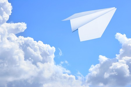 Paper plane flying against sky and clouds in the background  photo