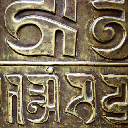 lamaism: Letters on buddhist prayer wheel close-up in a temple Stock Photo