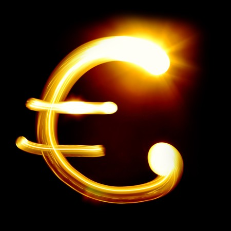 Euro sign created by light over black background photo