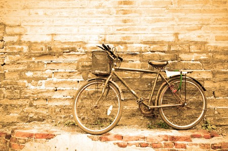 Lonely vintage bicycle near old brick wall sepia toned. photo