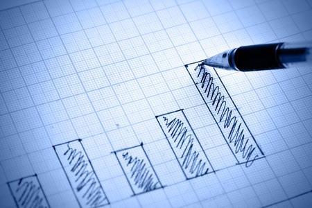 Pen drawing profit bar chart. Shallow DOF! Stock Photo