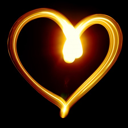 seasonal symbol: Heart symbol created by light over black background Stock Photo