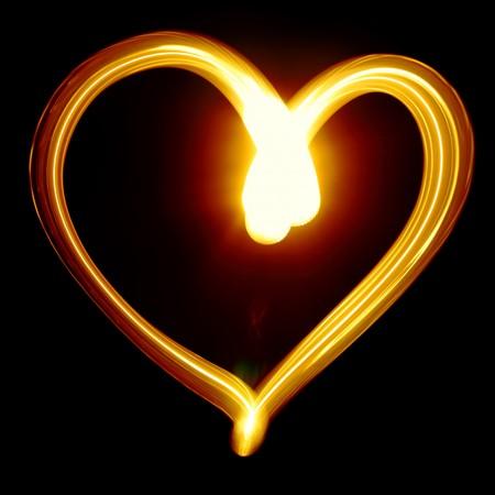 dessin coeur: Symbole de coeur cr�� par la lumi�re sur fond noir