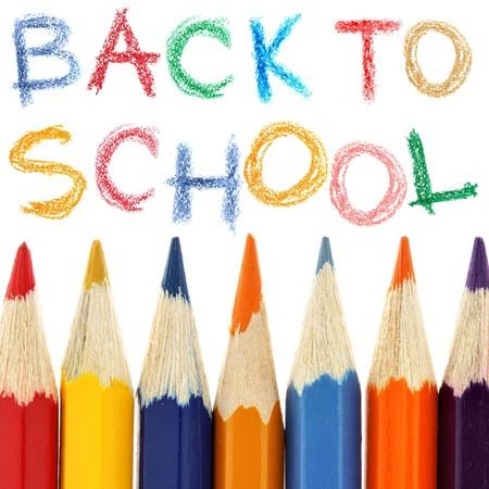 utiles escolares: L�pices de colores y la vuelta a la escuela texto sobre fondo blanco  Foto de archivo