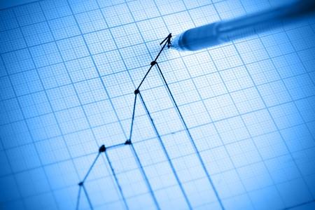 Pen drawing profit line graph. Shallow DOF! photo