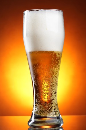 Glass of beer with froth over yellow background photo