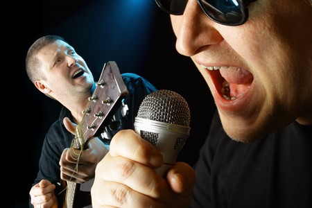 Two performers with microphone and guitar over black background  photo