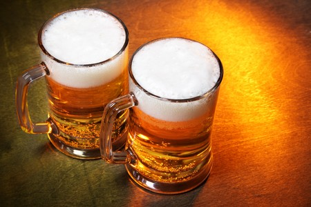 Beer mugs close up on wooden table  photo