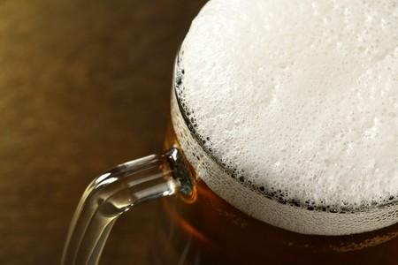 unbottled: Beer mug with froth over dark background  Stock Photo