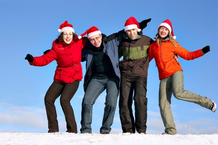 Friends with Santa hats have fun on flank of hill photo