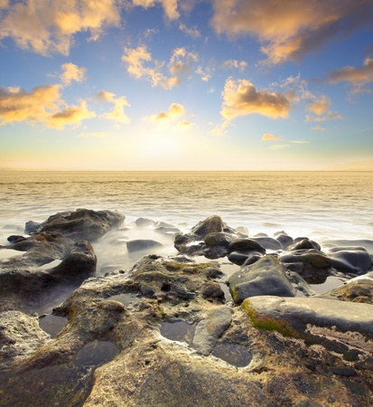 Beautiful sundown at rocky beach. Water in motion blur. photo