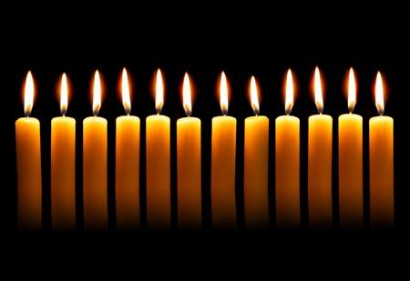 alight: Twelve alight candles over the black background Stock Photo