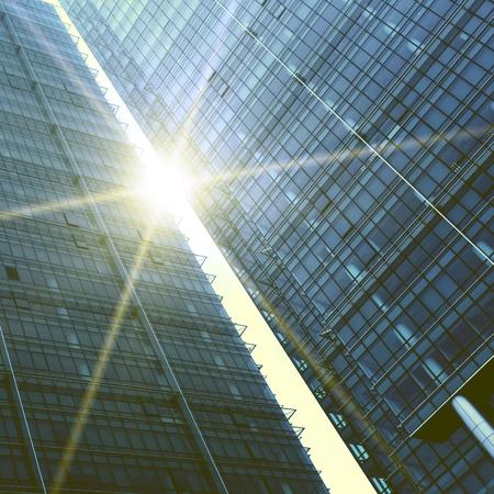 太陽のまぶしさを持つ 2 つの抽象的な高層ビル