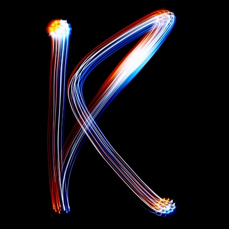 pictured: K - Created by light colorful letters over black background