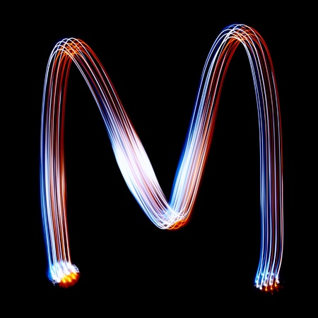 pictured: M - Created by light colorful letters over black background Stock Photo