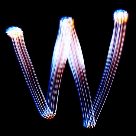 pictured: W - Created by light colorful letters over black background Stock Photo