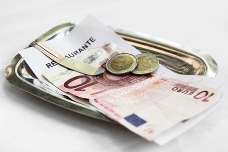 Restaurant bill and money on matal tray  Standard-Bild